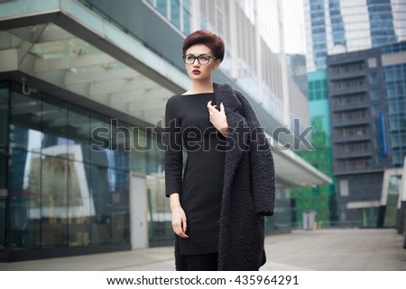 Beautiful young woman with glasses walking in the city