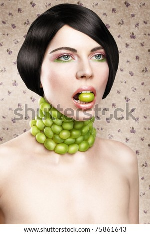 Beautiful young woman with green grape - stock photo