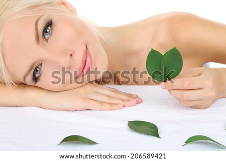 Beautiful young woman with green leafs isolated on white - stock photo