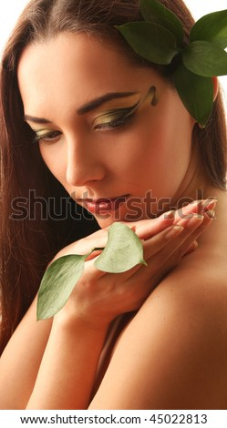 beautiful young woman with green leaves
