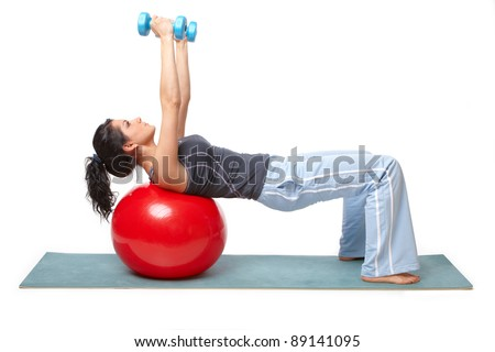 Beautiful young woman with gym ball exercising with dumb bells, isolated on white background