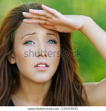 Beautiful young woman with hand closes eyes from sun and looks into distance, against background of summer green park. - stock photo