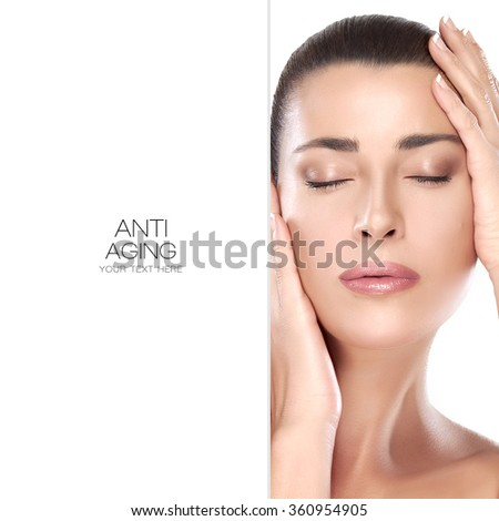 Beautiful young woman with hands on face, closed eyes with a serene expression suitable for skincare and spa concepts. Beauty portrait isolated on white with copy space alongside and sample text - stock photo