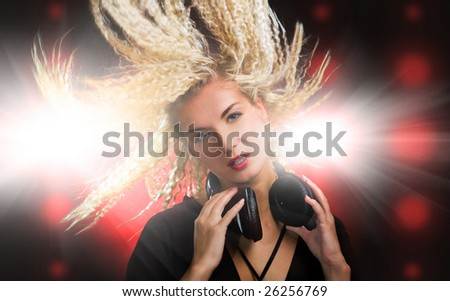Beautiful young woman with headphones in nightclub - stock photo