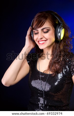 Beautiful young woman with Headphones listening music and smiling - stock photo