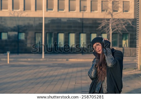 Beautiful young woman with headphones listening to music in the city streets
