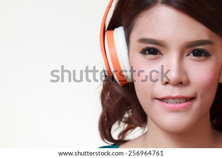 Beautiful young woman with headphones listening to the music - stock photo