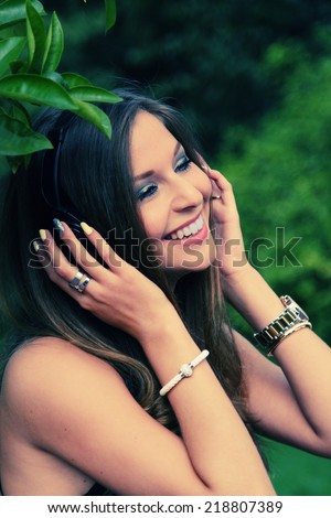 Beautiful Young Woman with Headphones Outdoors - stock photo