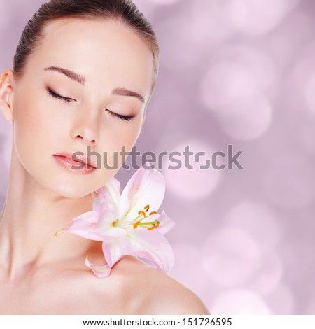 beautiful young woman with health skin and flower on her shoulder  - stock photo