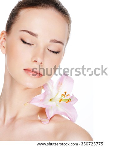 beautiful young woman with health skin and flower on her shoulder