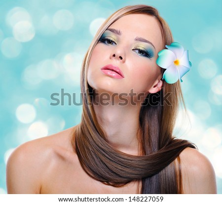 Beautiful young woman with healthy long hairs and flowers