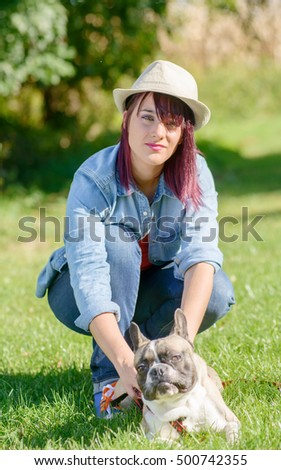 beautiful young woman with her dog french bulldog in the park