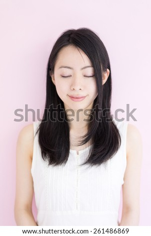beautiful young woman with her eyes closed against pink background - stock photo
