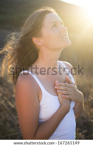 Beautiful young woman with her hands on her chest looking gratefully towards the sky. - stock photo
