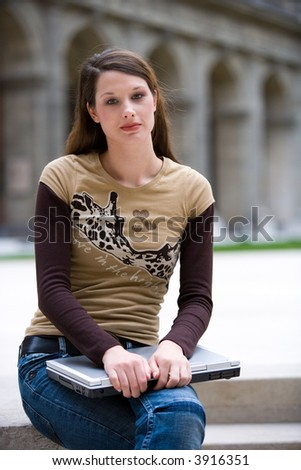 beautiful young woman with her notebook is sitting outside - stock photo