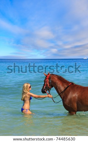 Beautiful young woman with horse on a tropical beach - stock photo