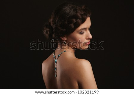 beautiful young woman with jewelry on back - stock photo