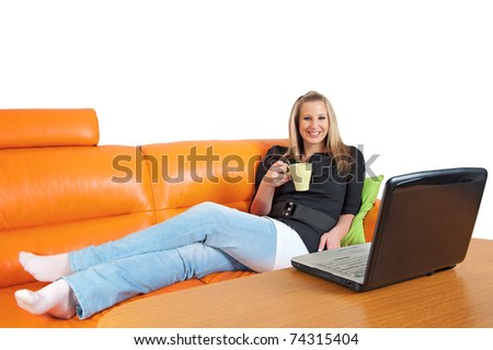 Beautiful young woman with laptop and cup of coffee relaxing on the sofa - stock photo