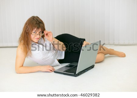 Beautiful young woman with laptop lying on the floor