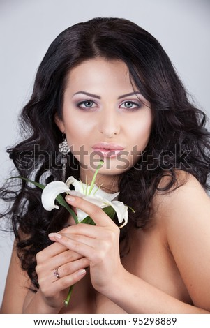 Beautiful young woman with lily flower. Close-up portrait - stock photo