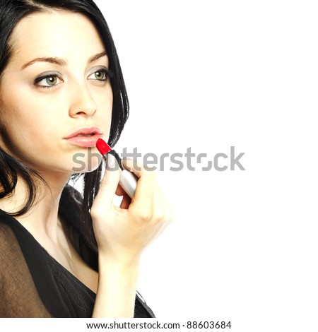 Beautiful young woman with lipstick in her hand with focus on face