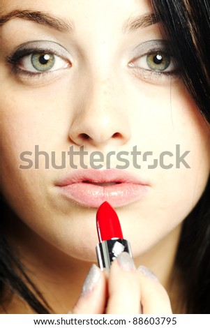 Beautiful young woman with lipstick in her hand with focus on face - stock photo