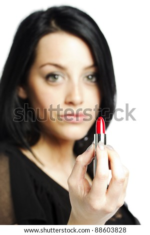 Beautiful young woman with lipstick in her hand with focus on lipstick - stock photo