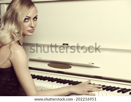 Beautiful young woman , with long blond hair , in elegant black dress , near a piano - stock photo