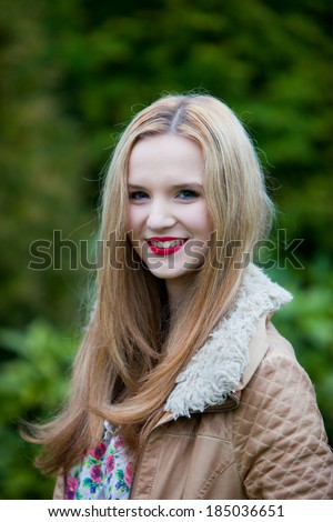 Beautiful young woman with long blond hair standing sideways outdoors in the garden turning to smile at the camera
