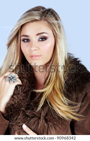 beautiful young woman with long blond hair wearing a suede fur coat on studio background - stock photo