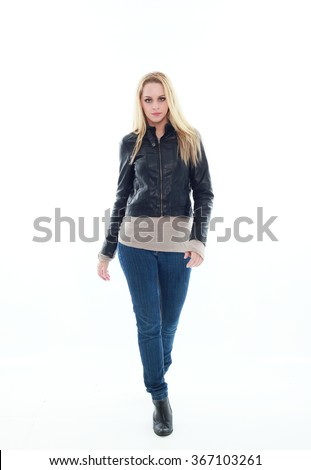 beautiful young woman with long blonde hair wearing black leather jacket and blue jeans.  standing pose, walking towards camera. isolated on white background. - stock photo