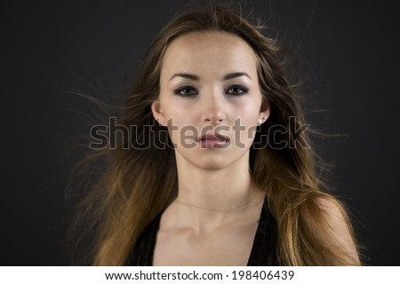 Beautiful young woman with long brown hair and a serious wistful expression on a dark background