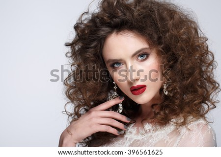 Beautiful young woman with long brown hair, red lips,jewellery in wedding dress Pretty model poses at studio.