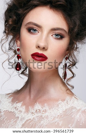 Beautiful young woman with long brown hair, red lips,jewellery in wedding dress Pretty model poses at studio. - stock photo