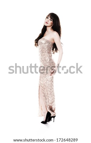 Beautiful young woman with long brunette hair posing standing sideways in an elegant metallic silver evening gown looking at the camera with a lovely smile, isolated on white - stock photo
