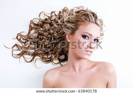 Beautiful young woman with long curly hair - stock photo