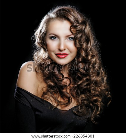 beautiful young woman with long curly hair against dark studio background - stock photo