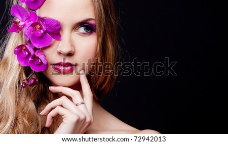 beautiful young woman with long curly hair and an orchid