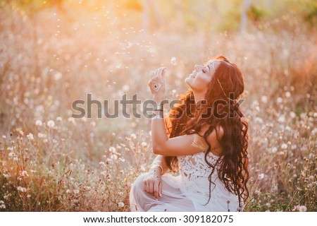 Beautiful young woman with long curly hair dressed in boho style dress posing in a field with dandelions - stock photo