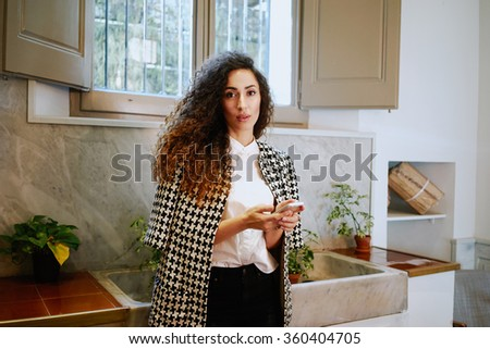 beautiful young woman with long curly hair text messaging and surfing the net with her smart-phone. attractive business woman holding a digital smartphone while text messaging - stock photo