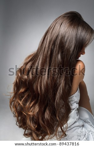 Beautiful young  woman with long curly hairs - stock photo