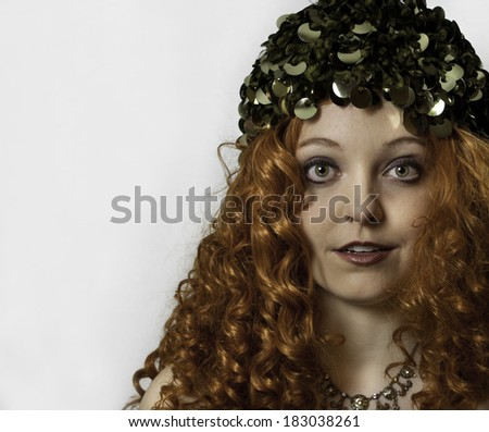 Beautiful young woman with long, curly red hair wearing green vintage hat and rhinestone necklace.