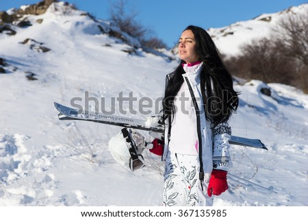 Beautiful young woman with long dark hair and eyes closed standing with skis and helmet as she takes in the sun on mountain