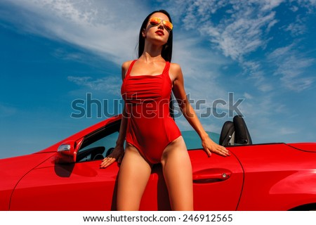 beautiful young woman with long dark hair in red bodysuit and sunglasses standing with red cabrio - stock photo