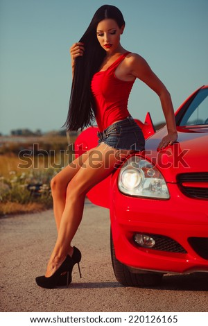 beautiful young woman with long dark hair in shorts sitting on the fender of red cabrio on the sunset - stock photo