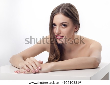 Beautiful young woman with long dark hair sitting at the table - stock photo