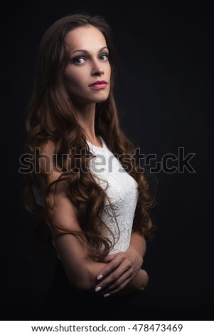 beautiful young woman with long hair on black background