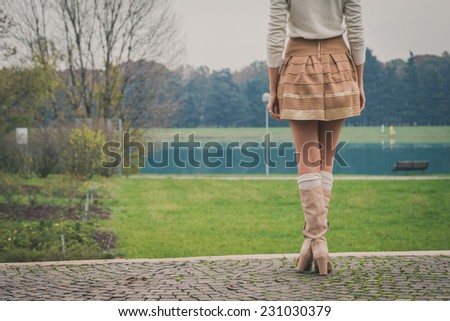 Beautiful young woman with long hair posing in a city park - stock photo