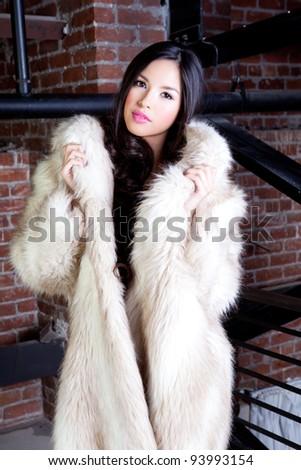 Beautiful Young Woman with long hair wearing a Faux fur coat - stock photo