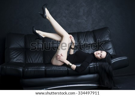 Beautiful young woman with long legs in bodysuit sitting on a black sofa - stock photo